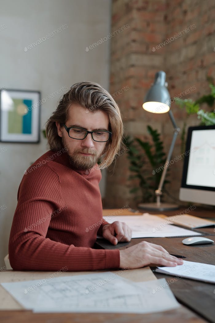 Young architect in glasses looking at sketch