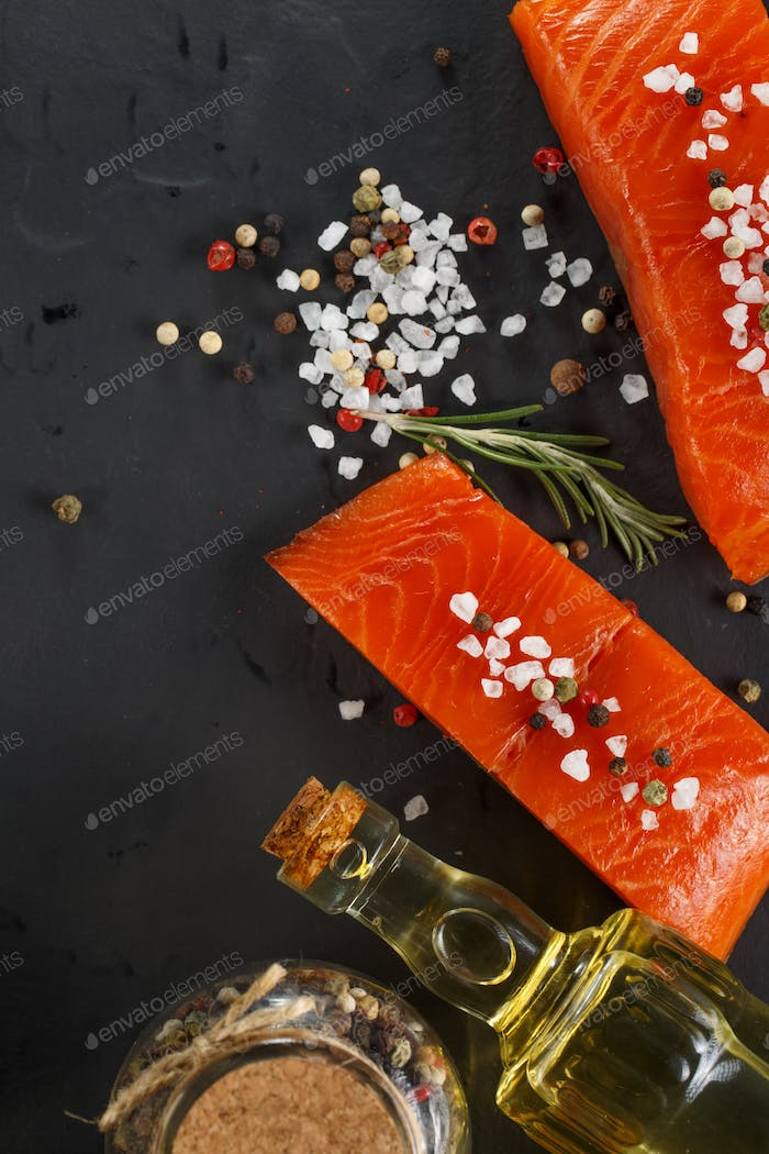 Two pieces Salmon with herbs on black background.