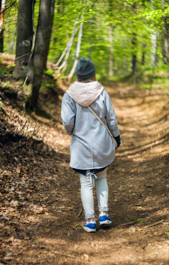 Young woman walking alone in early spring forest