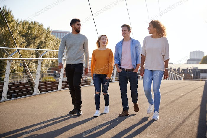 Group Of Young Friends Walking Across City Bridge Together