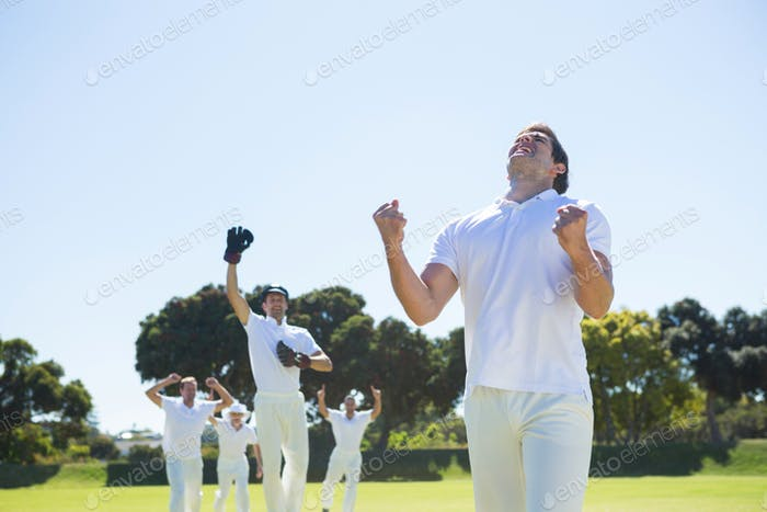 Happy cricket team enjoying victory while standing on field