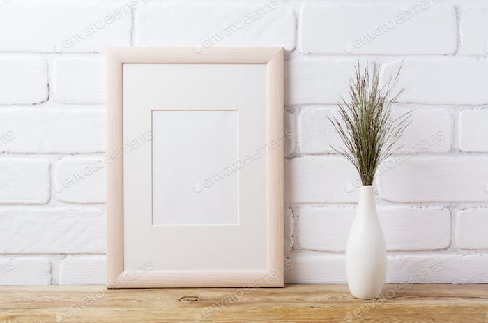 Wooden frame mockup with dark grass in elegant vase