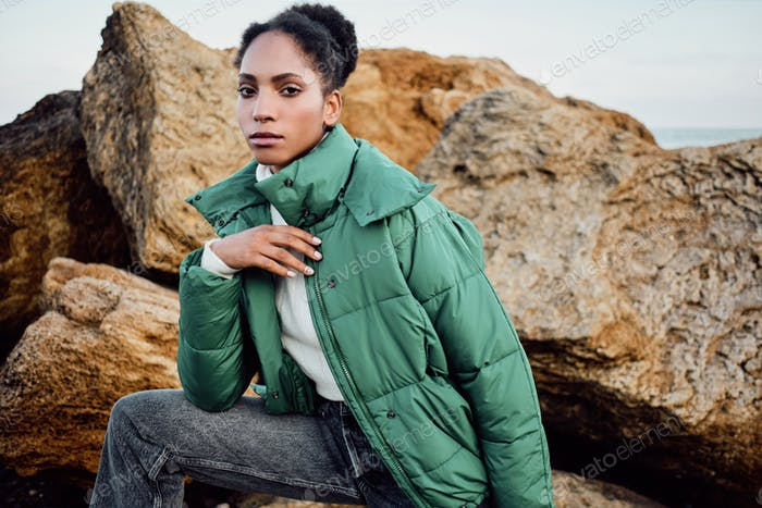 Gorgeous African American girl in stylish down jacket intently looking in camera on rocks by the sea