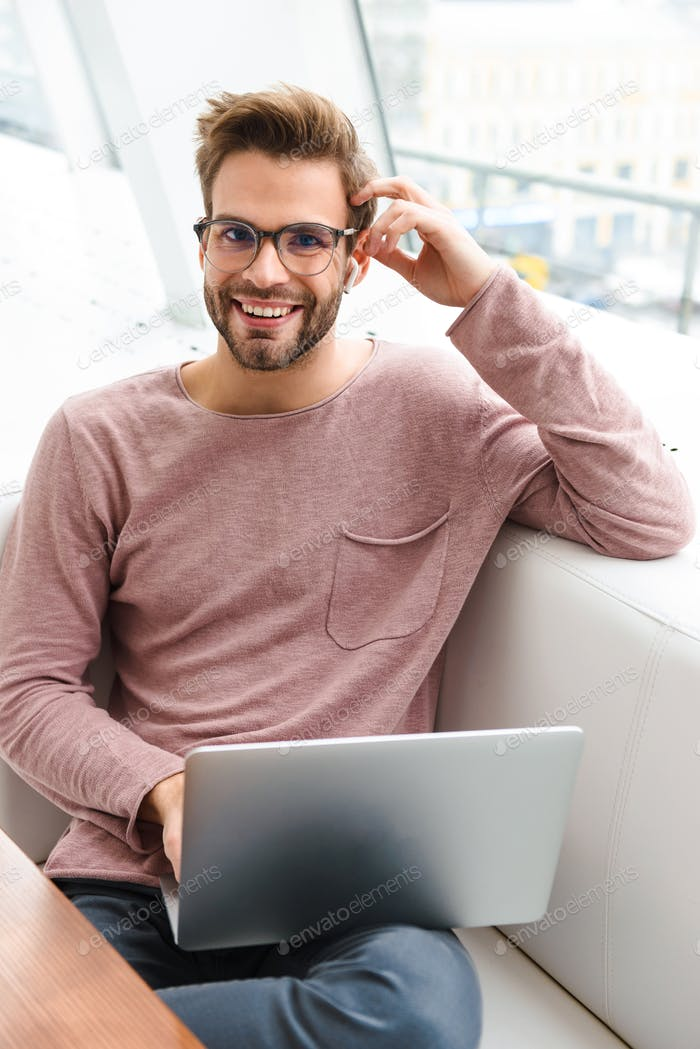 Image of man wearing earbuds working on laptop computer in cafe indoors