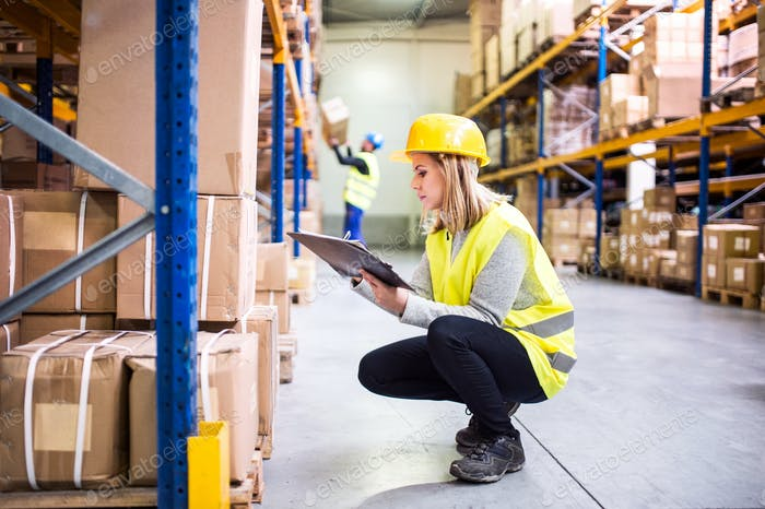 Woman warehouse worker with clipboard.