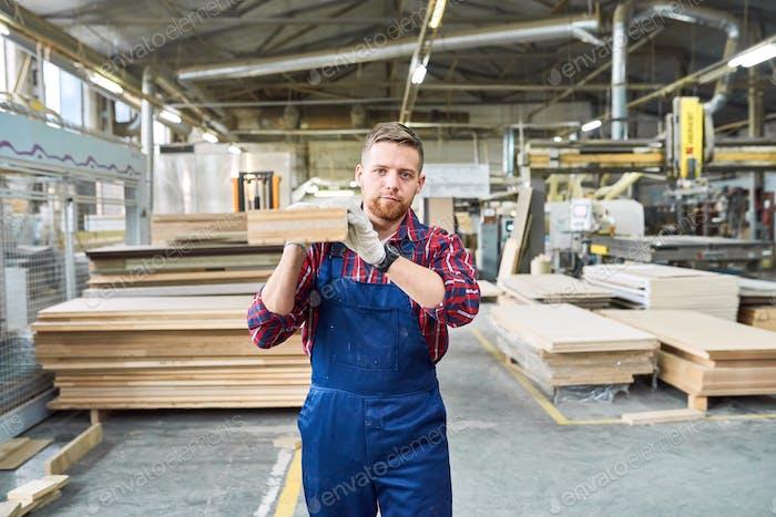 Junger Mann mit Holzbrett in der Fabrik
