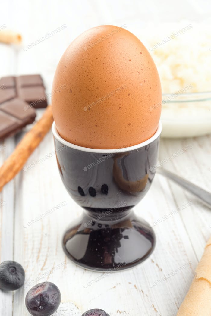 egg in black cup on white wood with chocolate and blueberries