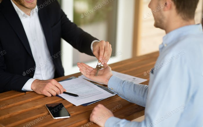 Closeup view of real estate agent giving house keys to male client at table