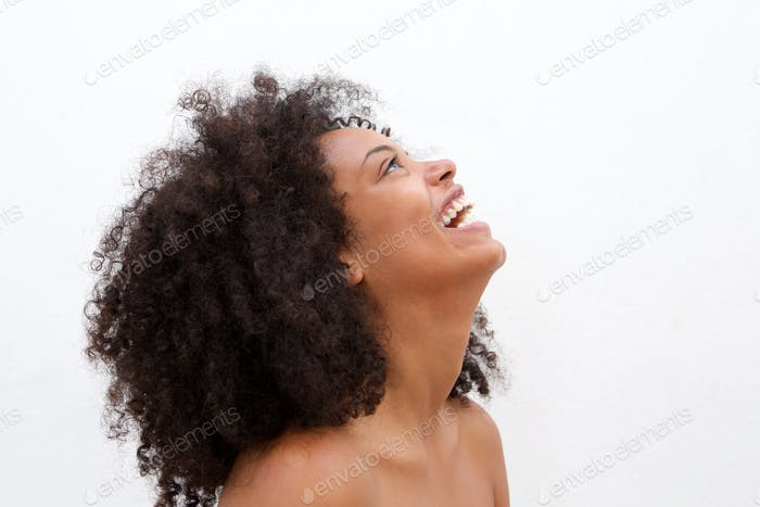 Side portrait of laughing black woman with bare shoulders