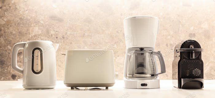 Kitchen electric appliances on white surface. Colorful, blurred background. Close up view, details.