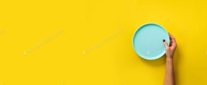 Female hand holding empty blue plate on yellow background with copy space. Healthy eating, dieting