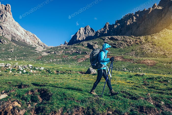 Woman with backpack hiking on high altitude mountains