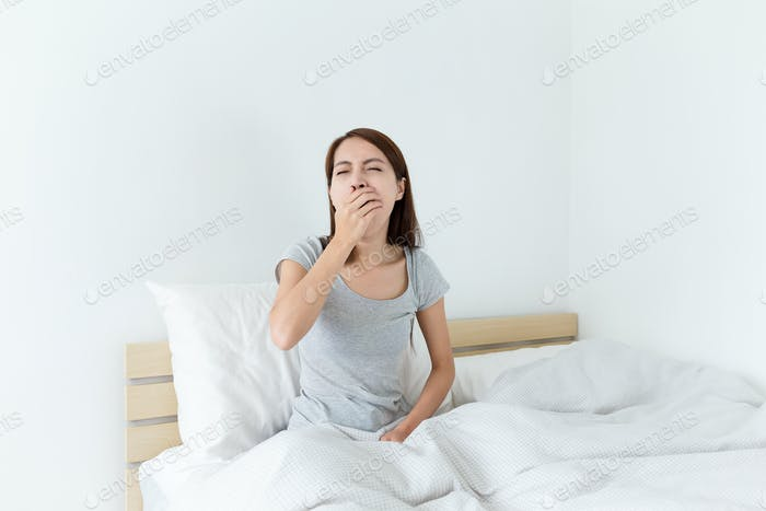 Young wake up yawning and hand cover her mouth