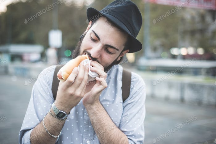 young handsome hipster gay modern man eating hot dog