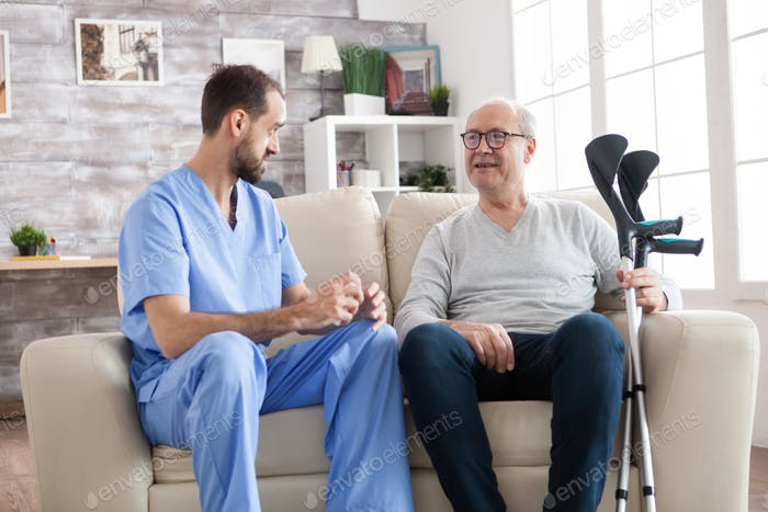 Elderly age man smiling while talking with male doctor