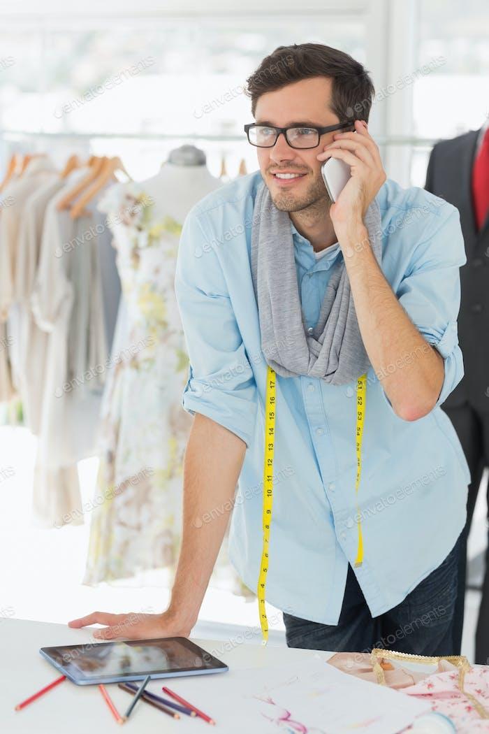 Smiling handsome male fashion designer using mobile phone in the studio