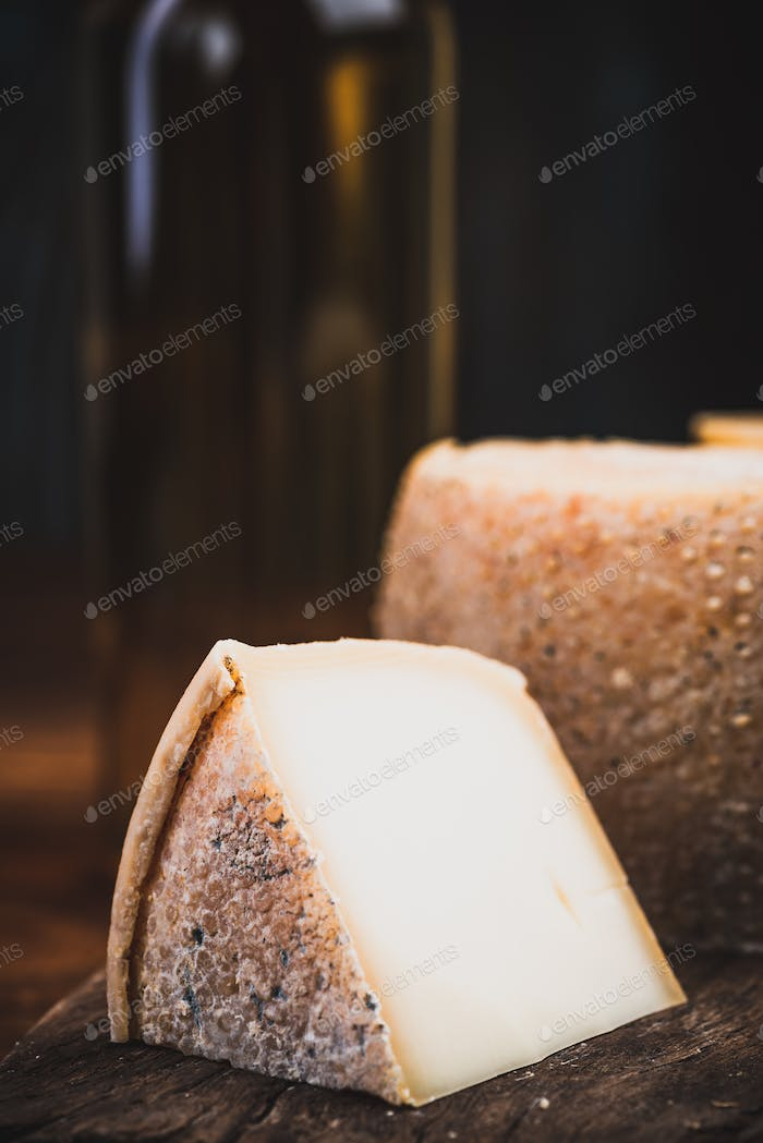 Slice of Hard Matured Cheese from Whole Cheese Wheel