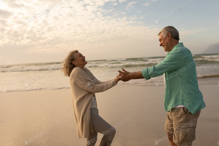 side view of active senior couple dancing together on the beach at dusk