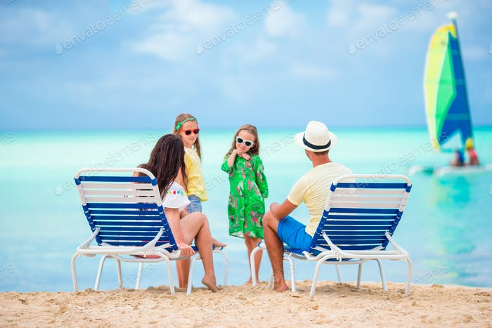 Happy beautiful family of four on the beach. Parents relaxing on sunbed and kids having fun on the