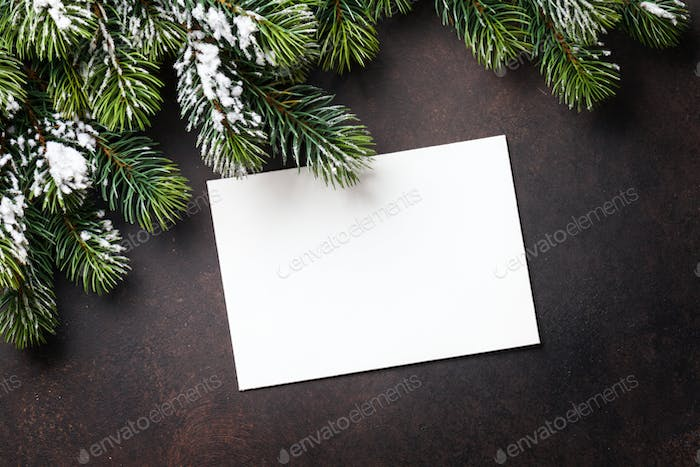 Christmas greeting card and fir tree over stone background