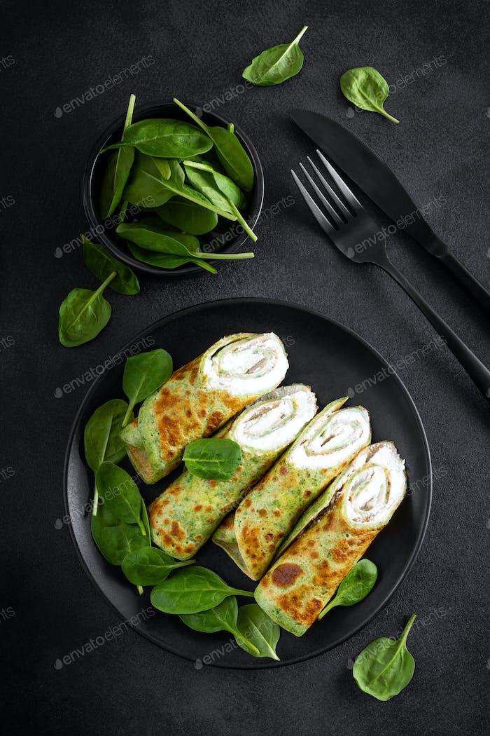 Savory crepes with spinach and feta cheese on black background, top view