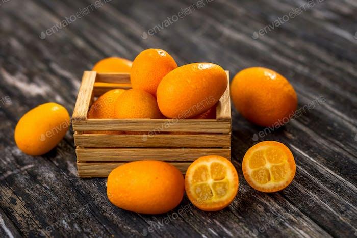 Raw Organic  Kumquats on wooden background