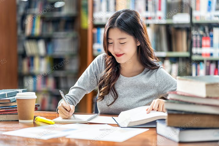 Asian young Student in casual suit reading and doing homework in library of university