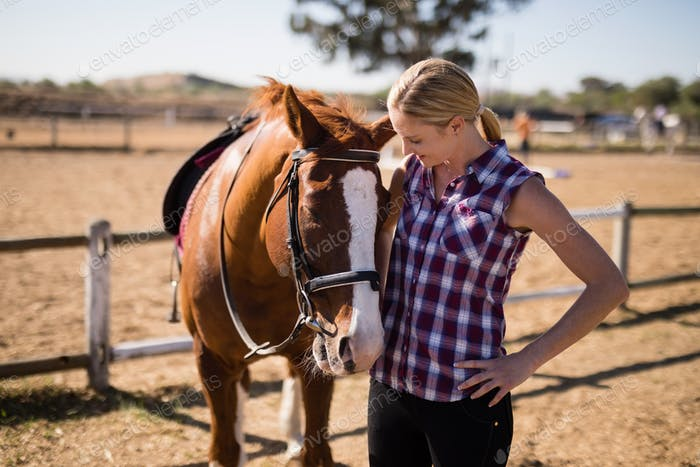 Smiling woman looking at horse