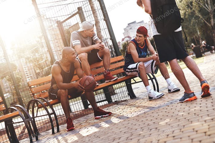 Weekend activities. Group of young men in sports clothing talking while spending time outdoors