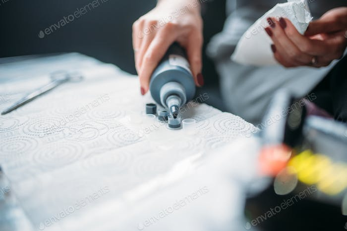 Female tattooist hands holds tattoo machine