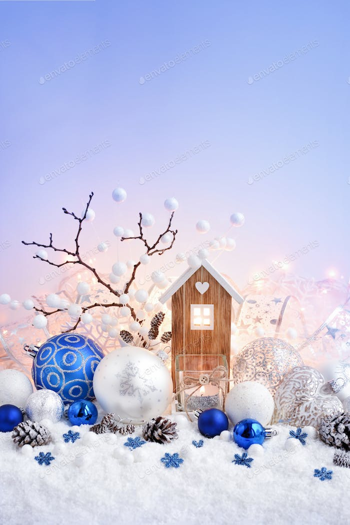 Christmas composition with decorative balls and toy house on sno