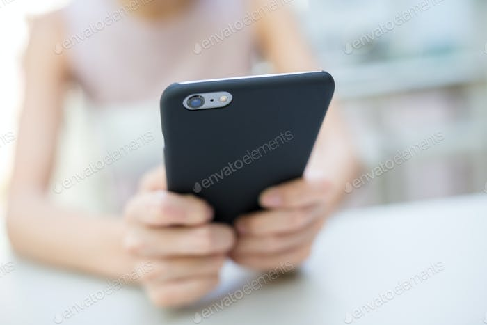 Woman sending sms on cell phone