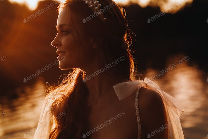 An elegant bride in a white dress enjoys nature at sunset.Model in a wedding dress in nature in the