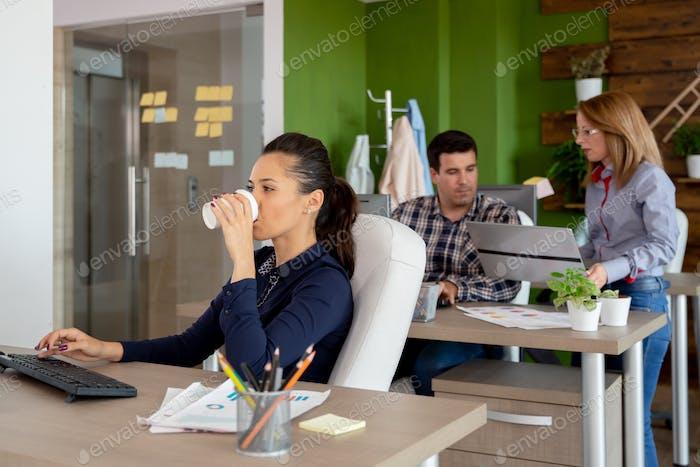 Великолепная бизнесвумен пьет кофе в оживленном стартап-офисе