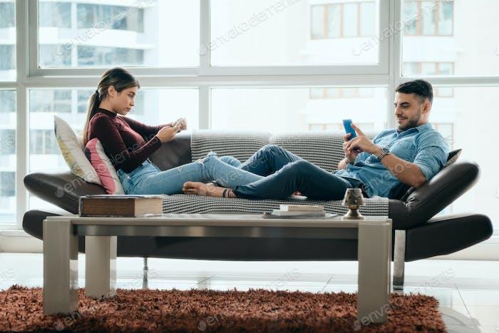 Junges Paar Ignorieren einander, während mit Smartphone