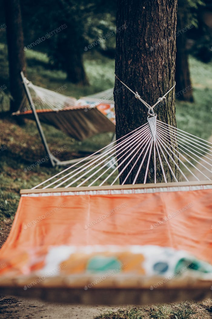 Comfortable orange hammock hanging outdoors in a park