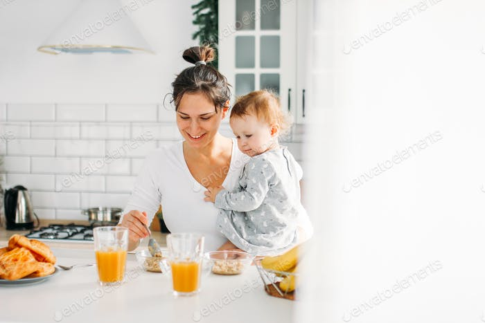 Young woman mom with baby girl on hands cooking breakfast on bright kitchen