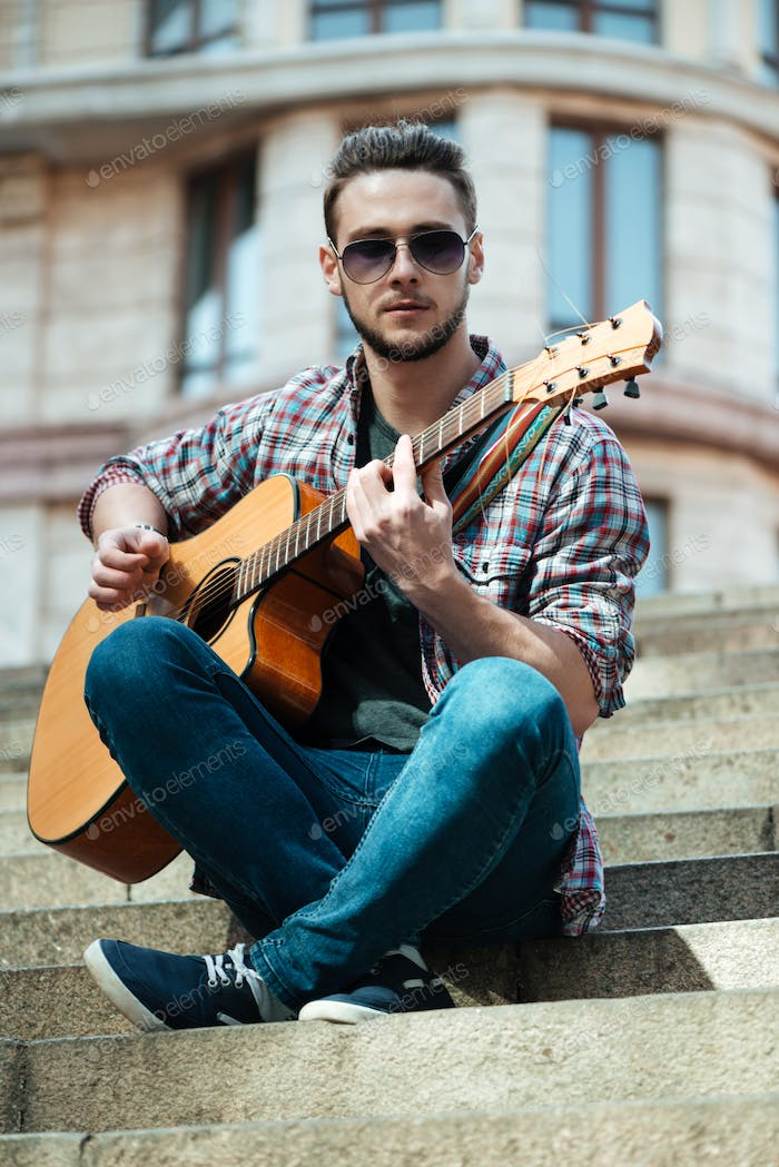 Man playing on the guitar outdoors