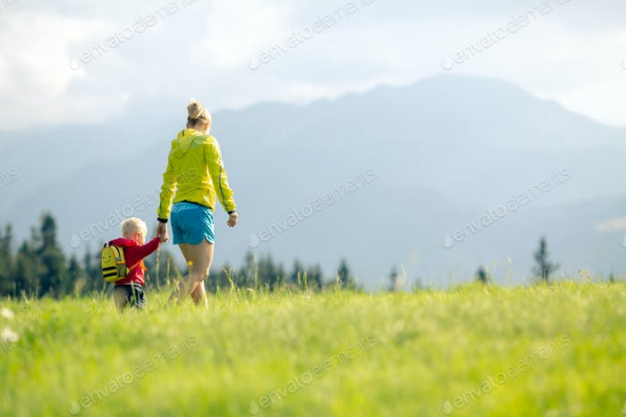 Happy mother with baby boy walking on green meadow.