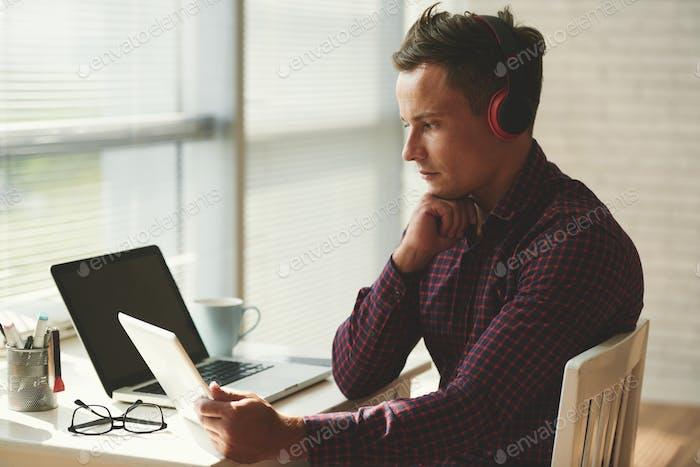 Man watching videos on digital tablet