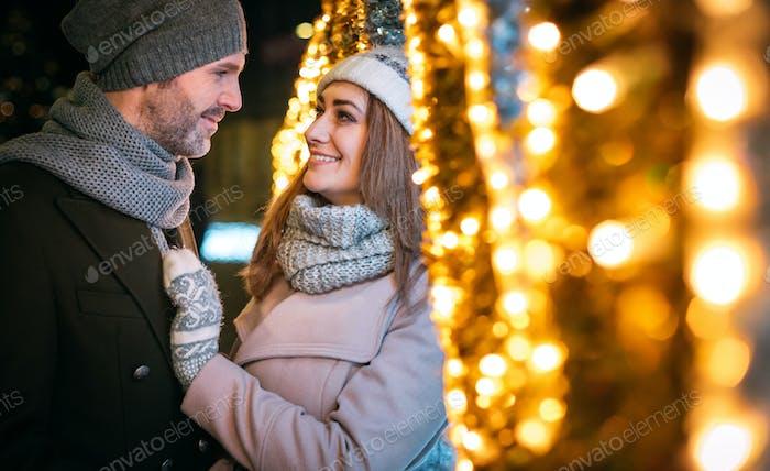 Loving couple hugs among Christmas street decorations