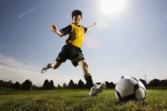 A soccer player, a boy preparing to kick a soccer ball.