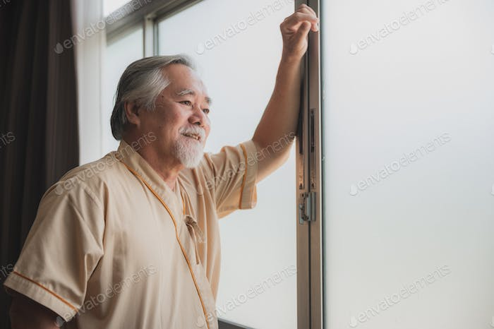 Eldery senior male patient standing and looking outside of the hospital window
