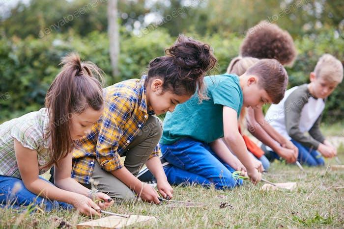 Gruppe von Kindern auf Outdoor-Camping-Reise Lernen, wie man Feuer macht