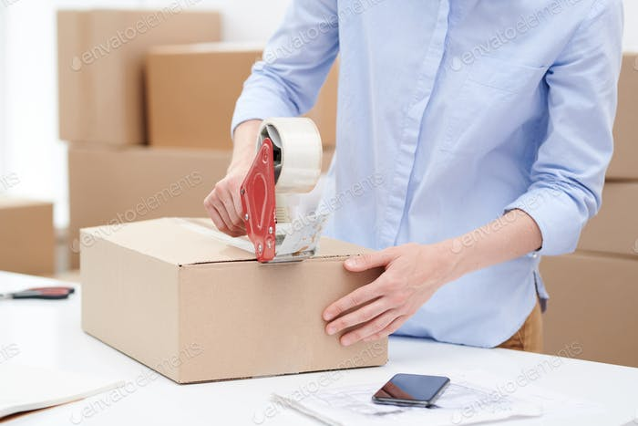 Young female sticking packed order of client with adhesive tape