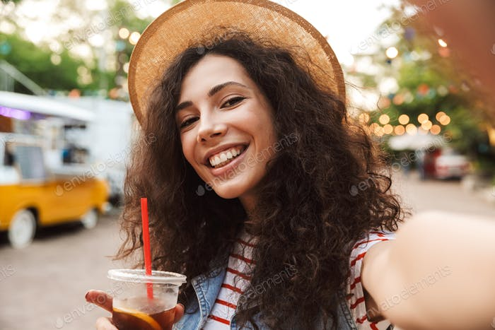 Photo of affable smiling woman 18-20 with curly brown hair weari