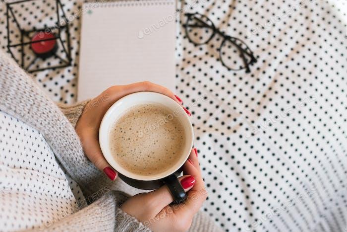 Schöne junge Frau trinken Kaffee Cappuccino, perfekte rote Gel-Lack Maniküre.