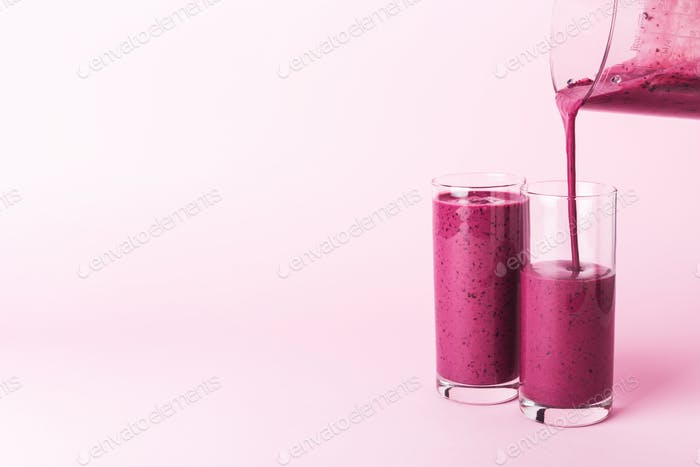 Two Glasses of Blueberrie Smothie on Pink Background.