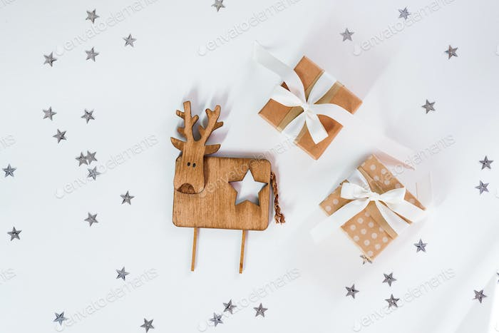 Small gift boxes with vintage wooden deer against a stars sparkling white background Christmas