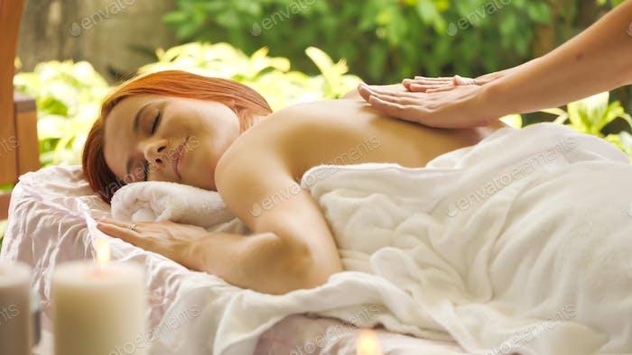 Beautiful caucasian woman getting back massage at spa.